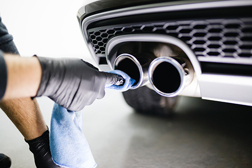 mechanic polishing new exhaust after fitting