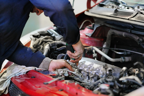 mechanic fixing a car with the bonnet open